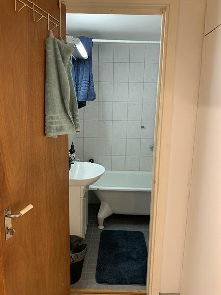Fräscht badrum med toalett, dusch, badkar, handfat och badrumsspegel.