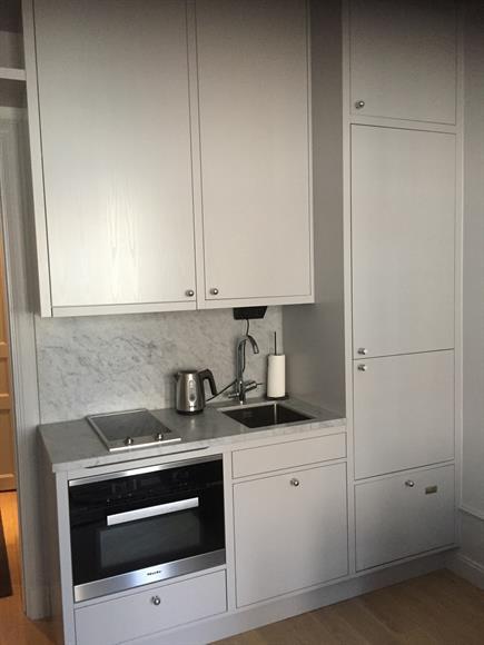 Köksdel med induktionshäll, ugn, micro, kyl/frys och diskmaskin.