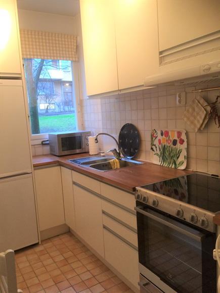 Kök med utfällbart bord och stolar från väggen. Kyl, frys, mikro, ny spis.