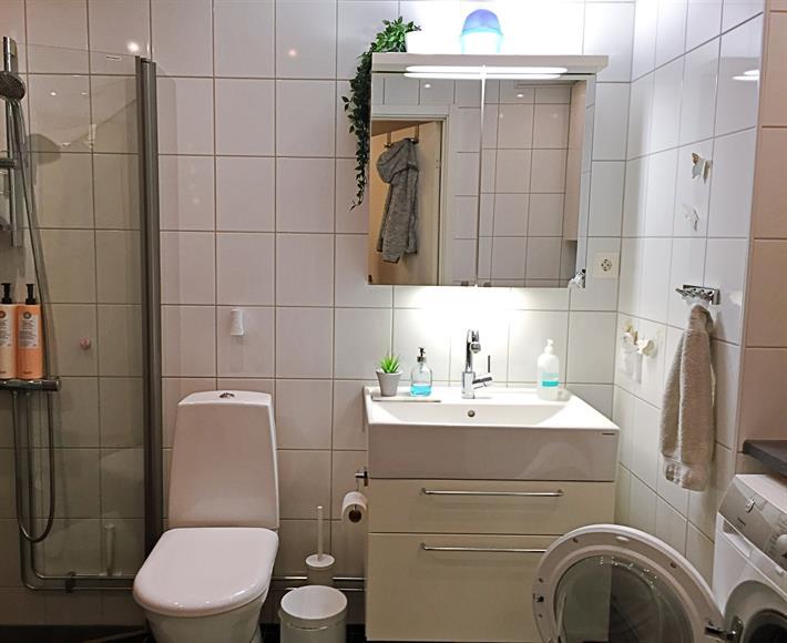 Stort och fräscht badrum med dusch, handdukstork, tvättmaskin och torktumlare.