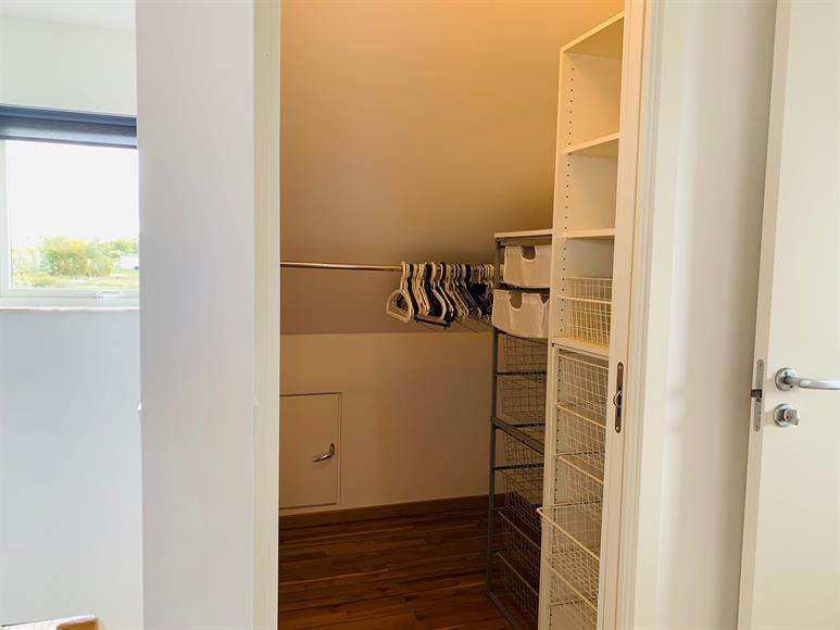 Till vänster om trappan ligger en praktisk walkin closet med tillhörande klädmoduler.  To the left of the stairs is a practical walk-in closet with built in clothing modules.