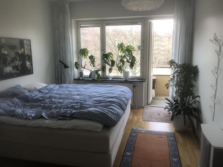 Sovrum med skön Carpe Diemsäng 210x210, lakan, täcke, påslakan och örngott ingår i hyran. Balkong ut mot stora Gubberoparken.