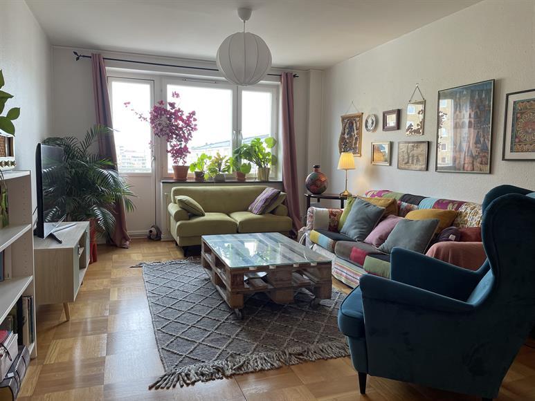 Vardagsrum med TV, en 2-sits och en 3-sitssoffa samt en fåtölj. Utgång till balkongen mot gatan.
