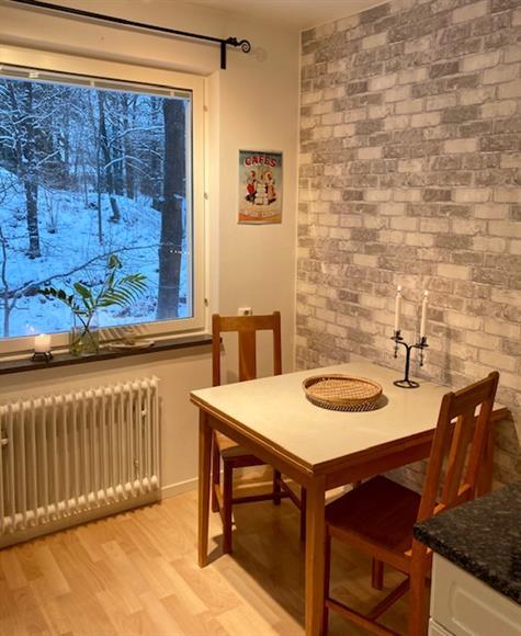 Matplats i köket. Iläggsskiva finns, samt 4 stolar. Utsikt mot skogsparti.