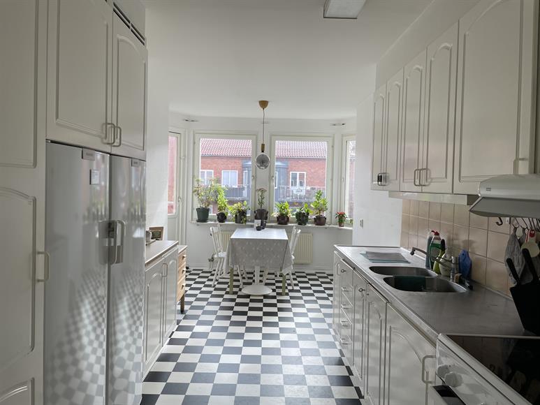 Kök med stor kyl och frys. Gott om förvaring och plats för stort matbord. Utgång till balkong ut mot innergården.