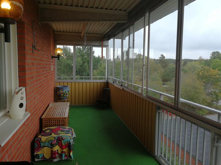 Stor balkong med utsikt över grönområden.