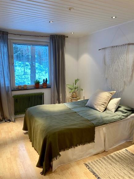 Sovrum med 140 cm säng. Utsikt mot skogsparti.