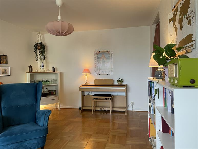 Andra halvan av vardagsrummet. Bokhyllor samt digitalpiano.
