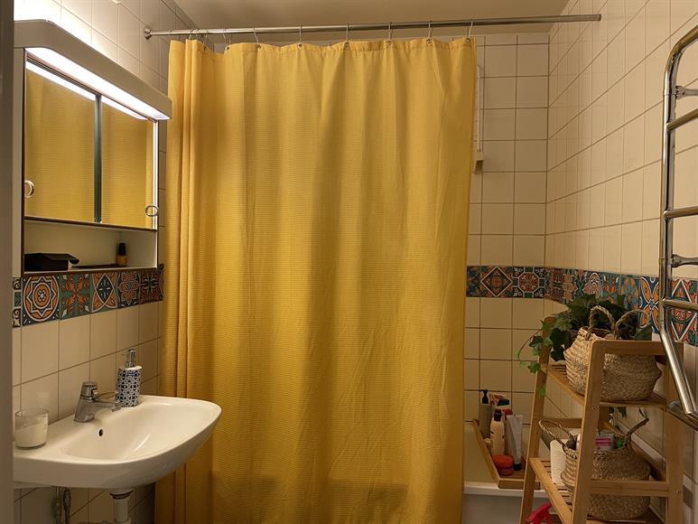Badrum med badkar och handdukstork.
