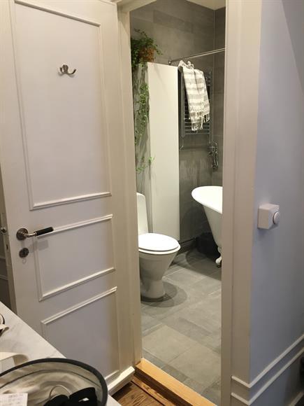 Rymligt badrum med badkar, tvättmaskin och förvaring.