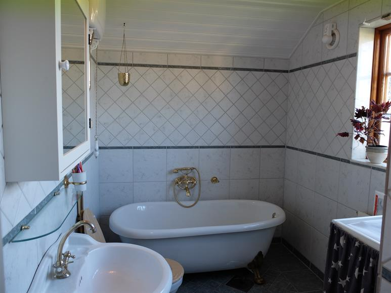 Badrum på ovanvåning, med bubbelbadkar, dusch och toalett.