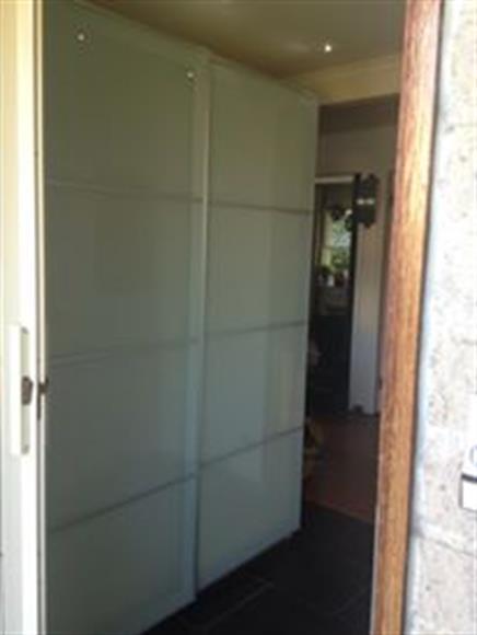 Ljus hall med garderober med skjutdörrar.