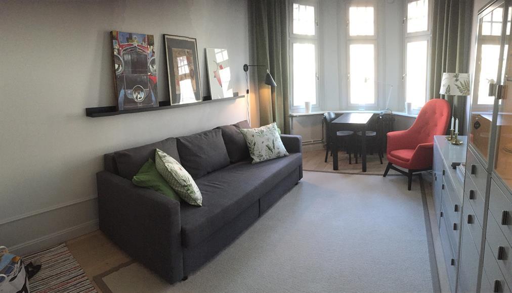 Mysigt rum med burspråk, soffa, matgrupp och skåp