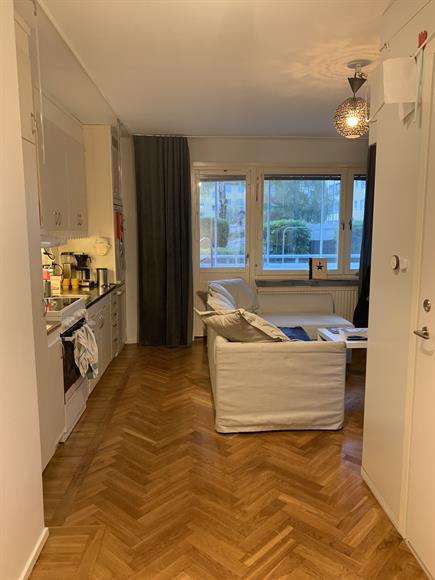 Direkt till vänster ser vi en liten skymt av det lilla sovrummet. I bild ser vi vardagsrummet och köket.
