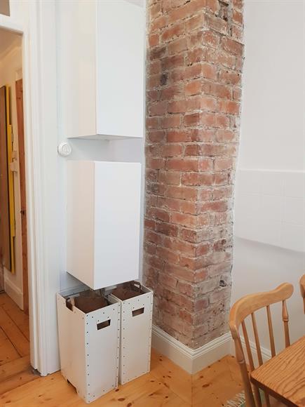 Tegelvägg i köket, och extra förvaringsskåp.