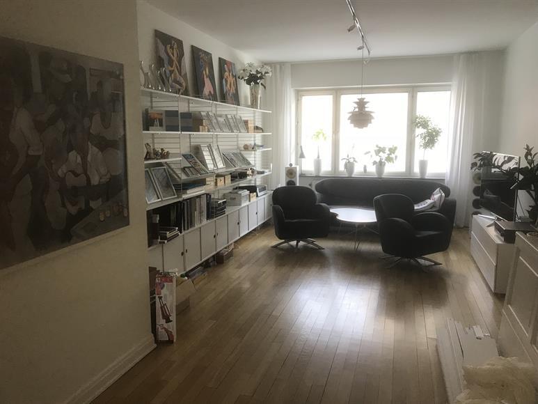 Stort vardagsrum med bokhylla, soffa, fåtöljer, bord och lampor.
