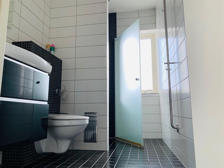 På vänster sida om hallen finner ni gästbadrummet med modern dusch, handfat och vägghängd toalett.   On the left side of the hall you will find the guest bathroom with modern shower, sink and wall attached toilet.