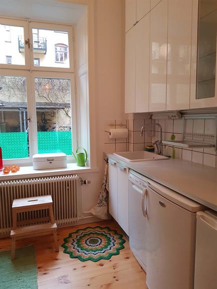 Modernt vit kök med massa förvaring och en sprillans ny diskmaskin.