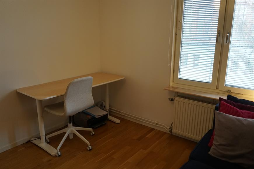 Bedroom 2, currently set as a home office with desk chair and double sofa bed plus large wardrobe storage space.