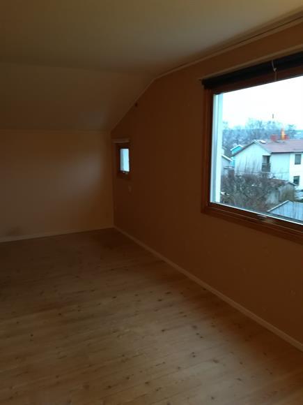 En del av tredje sovrummet på övervåningen, fönster mot trädgården.