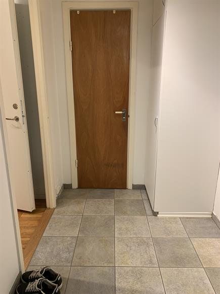 Hall med garderob. Rakt fram är badrummet och till vänster är vardagsrummet och sovrummet.