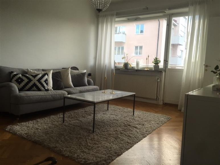 Vardagsrum med soffa, soffbord, tv samt tv möbel och två mindre bokhyllor. Ingen insyn och fantastiskt ljusinsläpp.