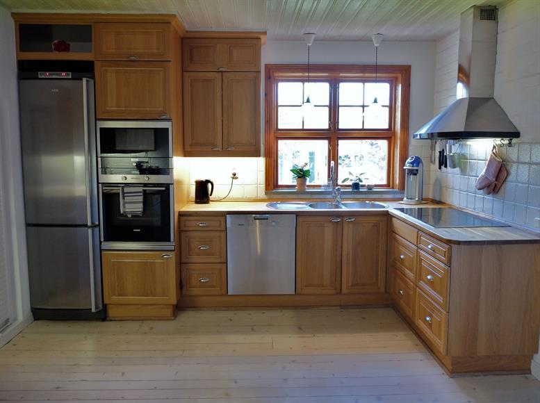 Kök med induktionshäll, micro, ugn och kyl och frys. med utsikt över grönskan.