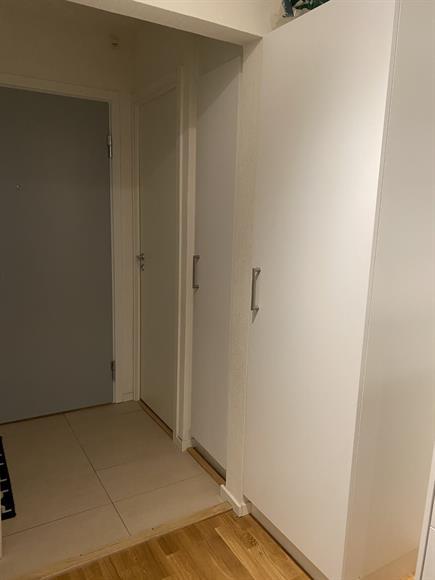 En liten garderob i hallen samt en städskrubb