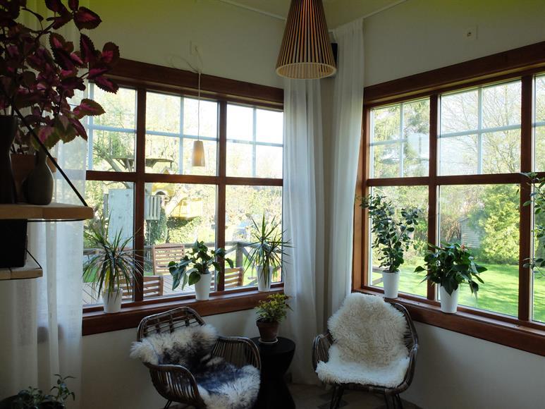 Tornrummet i anslutning till vardagsrummet, stora ljusa fönster med grönskande trädgård utandför.